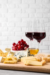 Cheese plate with honey, grapes and nuts on grey table, against brick wall
