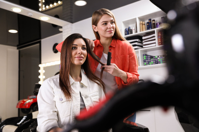Hairdresser making stylish haircut with professional scissors in salon