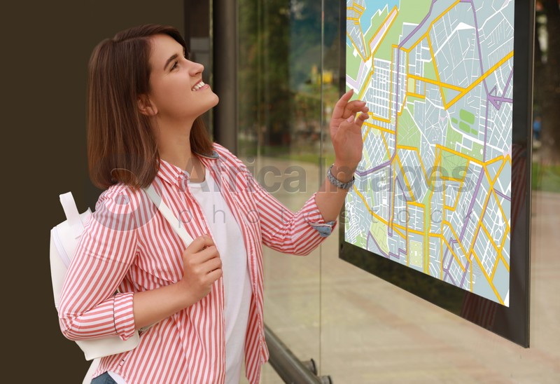 Young woman near public transport map at bus stop