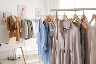 Collection of stylish women's clothes in modern boutique. Space for text