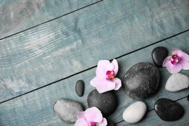Stones with orchid flowers and space for text on blue wooden background, flat lay. Zen lifestyle