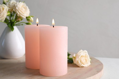 Burning candles and beautiful roses on white table