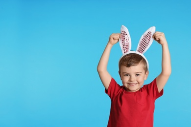 Portrait of little boy in Easter bunny ears headband on color background, space for text