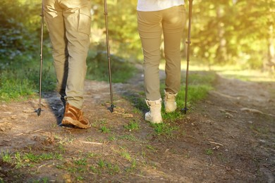 Couple with trekking poles hiking in forest, closeup