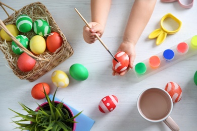 Little child painting Easter eggs on wooden background, top view