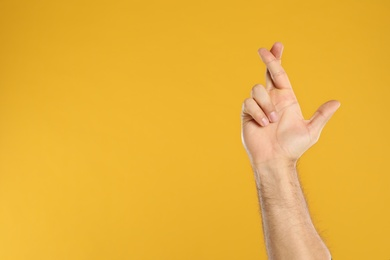 Man with crossed fingers and space for text on yellow background, closeup. Superstition concept