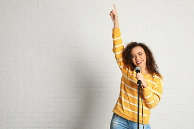Portrait of curly African-American woman singing in microphone near brick wall. Space for text
