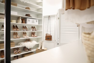 Dressing room interior with stylish shoes and accessories on shelves