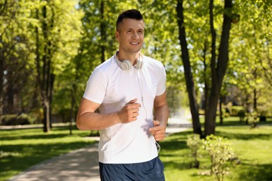 Young man with headphones on morning run in park. Fitness lifestyle