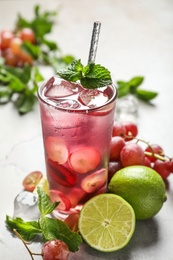 Soda water with grapes, ice, lime and mint on table. Refreshing drink