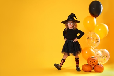 Cute little girl with pumpkins and balloons wearing Halloween costume on yellow background. Space for text