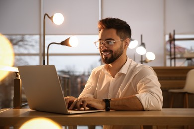 Man working with laptop at table in office