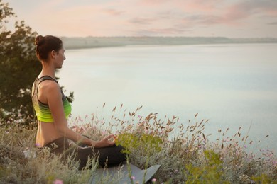 Woman meditating in meadow near river. Space for text