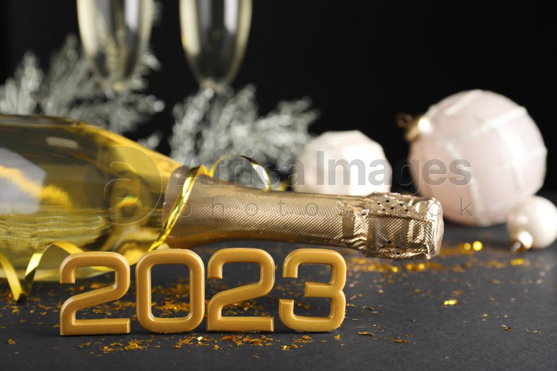 Happy New Year 2023! Bottle of sparkling wine and festive decor on table against black background