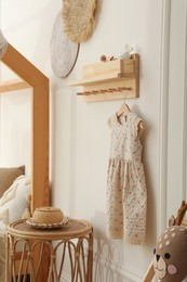 Wooden rack with cute dress in child room. Interior design