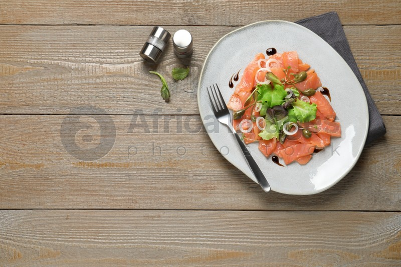 Delicious salmon carpaccio served on wooden table, flat lay. Space for text