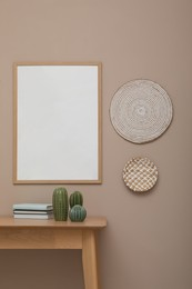 Empty frame hanging on beige wall over wooden table with decor. Mockup for design