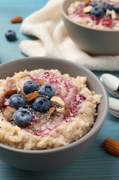 Tasty oatmeal porridge with toppings on light blue wooden table, closeup