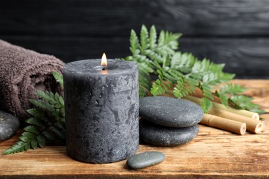 Composition with burning candle and spa stones on wooden table