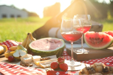 Picnic blanket with delicious food and drinks outdoors on sunny day, closeup