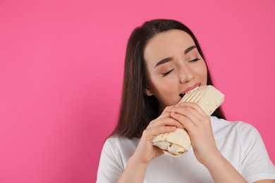 Young woman eating tasty shawarma on pink background. Space for text