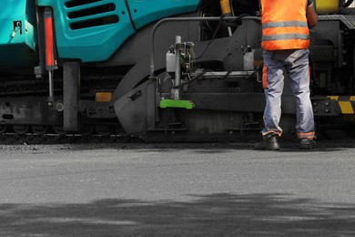 Worker working with asphalt finisher on city street, closeup. Road repair service