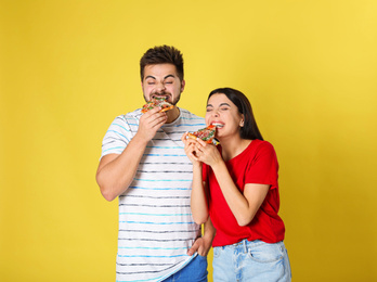 Emotional couple eating pizza on yellow background