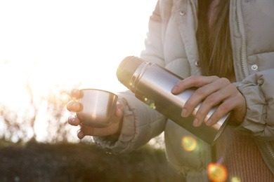 Woman pouring hot drink into cup from thermos outdoors, closeup