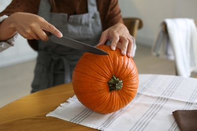 Woman carving pumpkin at table in kitchen. Halloween celebration