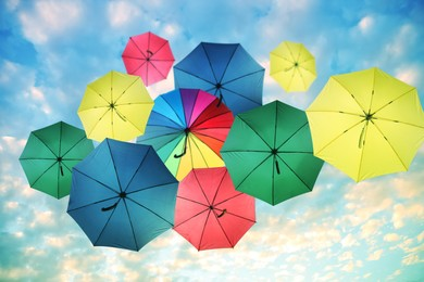 Group of different colorful umbrellas against blue sky with white clouds on sunny day, bottom view