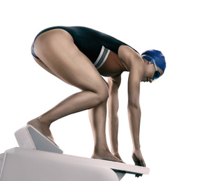Young athletic woman preparing for jump from swimming starting block on white background