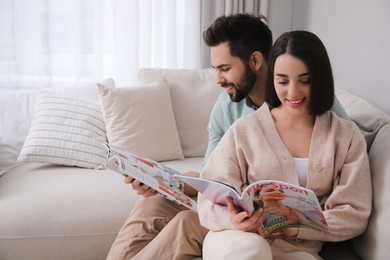 Young couple reading modern magazines on sofa at home, space for text