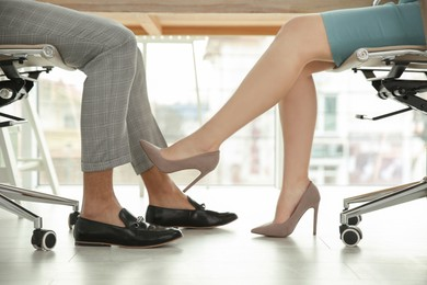 Young woman flirting with her colleague during work in office, closeup