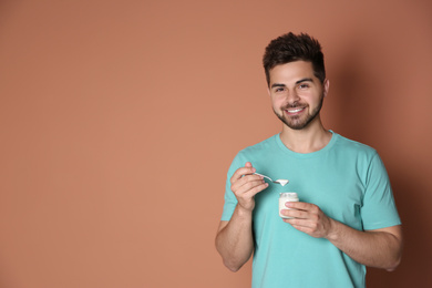 Happy young man with yogurt and spoon on brown background. Space for text