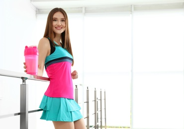 Young woman with protein shake indoors. Space for text