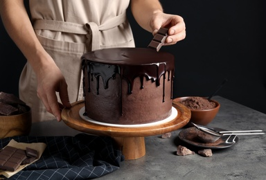 Chef making fresh delicious chocolate cake at grey table, closeup