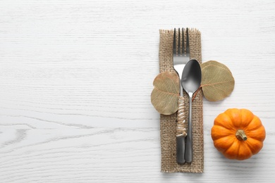 Cutlery with leaves, pumpkin and space for text on white wooden background, flat lay. Table setting elements
