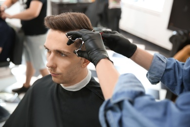 Professional barber working with client in hairdressing salon. Hipster fashion