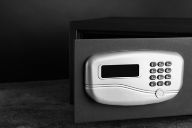 Black steel safe with electronic lock on grey table against dark background, closeup