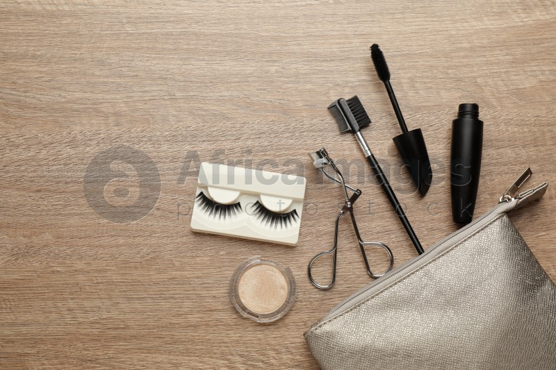 Flat lay composition with eyelash curler, cosmetic bag and makeup products on wooden table. Space for text