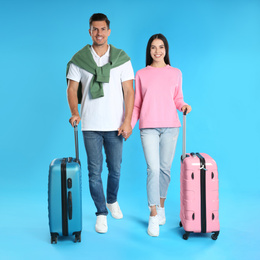 Happy couple with suitcases for summer trip on blue background. Vacation travel