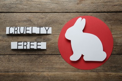 Cards with text Cruelty Free and figure of rabbit on wooden table, flat lay. Stop animal tests