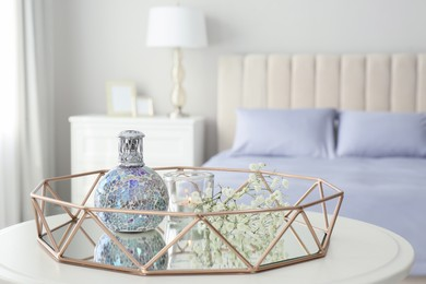 Stylish catalytic lamp with burning candle and gypsophila on table in bedroom. Cozy interior