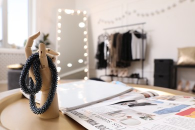 Wooden mannequin hand with necklace and magazines on golden table. Dressing room interior
