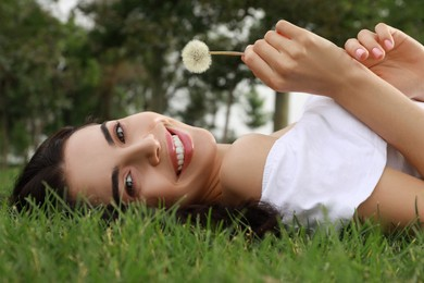 Beautiful young woman with dandelion lying on green grass in park. Allergy free concept