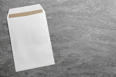 White paper envelope on grey background, top view. Space for text