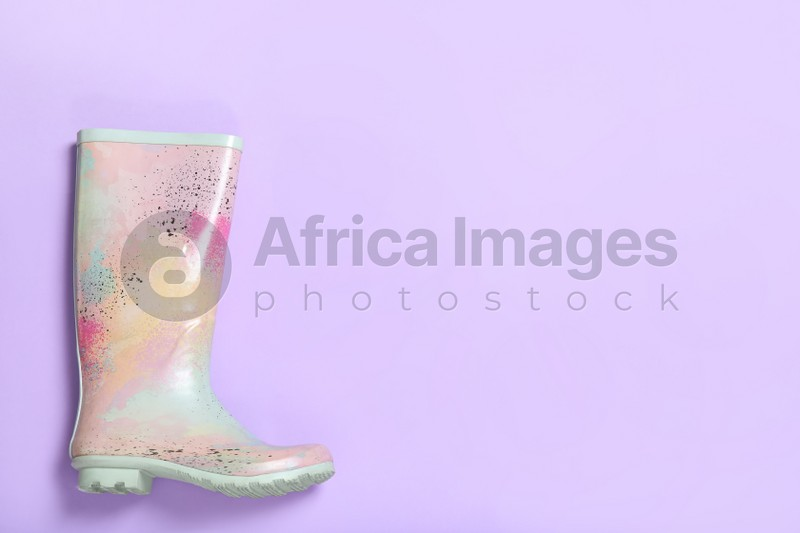 Colorful rubber boot on violet background, top view. Space for text