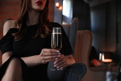 Elegantly dressed woman with glass of champagne in armchair indoors, closeup. Luxury lifestyle