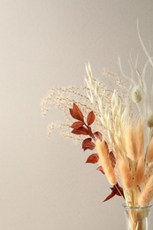 Dried flowers in vase against light background