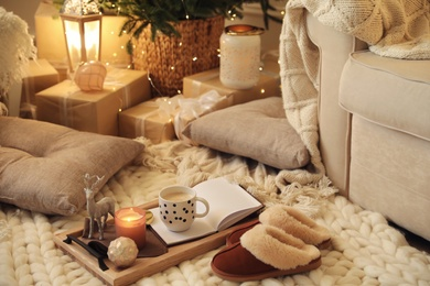 Wooden tray with cocoa, candle and notebook in room decorated for Christmas